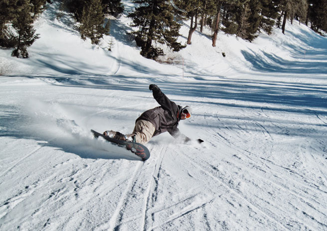 Athletic man snowboarding on mountain
