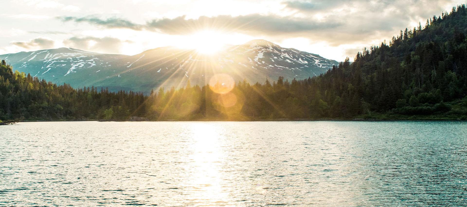 Sun setting over mountain lake